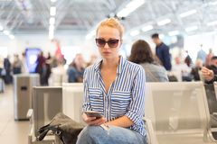 Woman using her cell phone while waiting to board a plane at departure gates at international airport. Royalty Free Stock Image