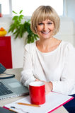 Casual blonde businesswoman in office Royalty Free Stock Image