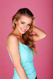 Casual Blonde Girl With Big Smile. Wearing a blue summer top posing on a pink studio background stock images