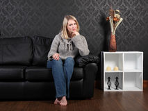 Casual blonde girl home relaxing on leather couch Royalty Free Stock Images