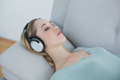 Casual blonde woman listening to music lying on couch Royalty Free Stock Photography