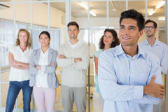 Casual boss smiling with arms crossed in front of business team Stock Images