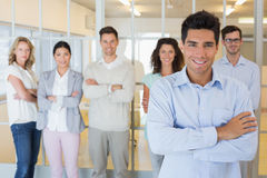 Casual boss smiling at camera in front of business team Stock Photos