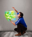 Casual boy holding laptop with recycle and environmental symbols Stock Photography