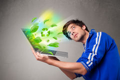 Casual boy holding laptop with recycle and environmental symbols Royalty Free Stock Photography