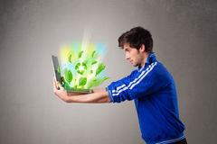 Casual boy holding laptop with recycle and environmental symbols Stock Photo