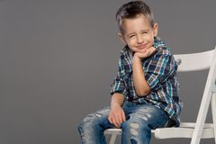 Casual boy with smile sitting om chair. Over a grey background Royalty Free Stock Images