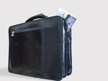 A Casual Briefcase and a Newspaper Inside It. A black casual leather briefcase, and a newspaper partly outside it royalty free stock images