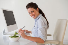 Casual brunette businesswoman eating a salad at her desk Stock Photo