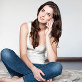Casual brunette girl holding cell phone Royalty Free Stock Photos