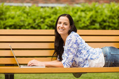 Casual brunette lying on bench typing on laptop Royalty Free Stock Photography