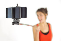 Casual brunette using selfie stick Royalty Free Stock Images