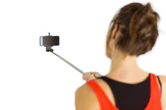Casual brunette using selfie stick Royalty Free Stock Photos
