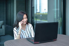 Casual Business Asian Woman phoning in front of a laptop in condo stock photo