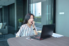 Casual Business Asian Woman yawning and working in front of a la Stock Photos