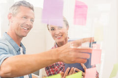 Casual business colleagues reading sticky notes Royalty Free Stock Image