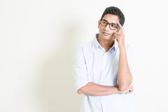 Casual business Indian male serious thought. Portrait of handsome casual business Indian man thinking with serious face expression, standing on plain background Royalty Free Stock Photos