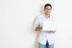 Casual business Indian male using laptop Stock Images
