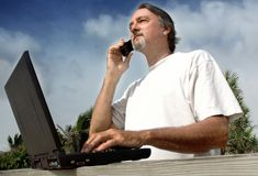 Casual business man. A casual entrepreneurial business man works outside using a cell phone and a black laptop computer Stock Images