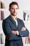 Casual Business Man. With arms crossed with a bookshelf behind him Royalty Free Stock Images