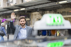 Casual business man catch taxi. Handsome man hailing a cab at train station Stock Image