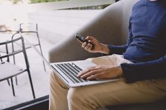 Casual business man or freelancer working on laptop computer and. Using mobile smart phone. Man internet browsing on phone in the morning, working from home Stock Images