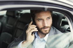 Casual business man on mobile phone in rear of the car royalty free stock image
