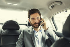 Casual business man on mobile phone in rear of the car Royalty Free Stock Photo