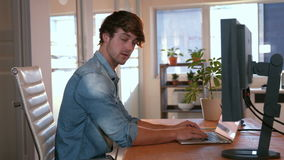 Casual business man using laptop computer and looking at camera stock footage