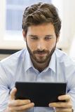 Casual business man working on tablet computer in office Stock Photography
