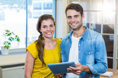 Casual business partners holding tablet and looking at camera Royalty Free Stock Images