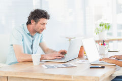 Casual business partners looking at laptop Stock Images