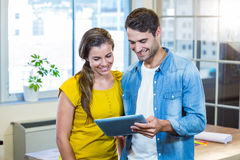 Casual business partners looking at tablet Stock Image