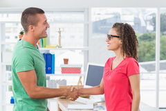 Casual business partners shaking their hands Stock Images