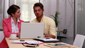 Casual business partners working together on laptop. In the office stock video footage