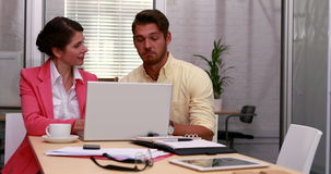 Casual business partners working together on laptop. In the office stock video
