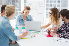 Casual business people around conference table in office. Young casual business people sitting around conference table in a bright office stock image