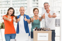 Casual business people donating and doing thumbs up Stock Photo