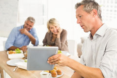 Casual business people looking at tablet while lunch Royalty Free Stock Image