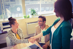 Casual business people shaking hands at desk and smiling Royalty Free Stock Image