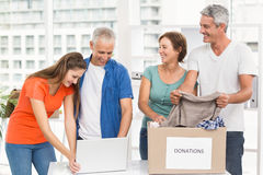 Casual business people sorting donations. In the office royalty free stock image