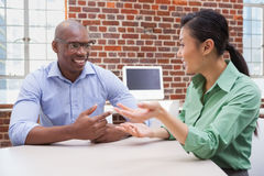 Casual business people talking at desk and smiling. In the office Stock Images