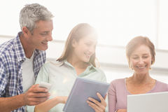 Casual business people using electronic devices Stock Images