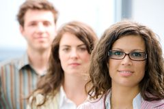 Casual business team. Happy young casual business people standing in a row, smiling royalty free stock images