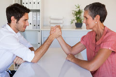 Casual business team arm wrestling at desk Stock Images