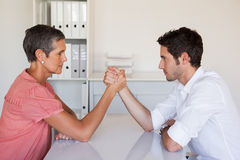 Casual business team arm wrestling at desk Royalty Free Stock Photography