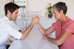 Casual business team arm wrestling at desk Royalty Free Stock Photos