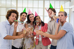 Casual business team celebrating with champagne and party horns Stock Photos