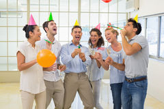 Casual business team celebrating with champagne and party poppers Royalty Free Stock Image