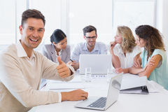 Casual business team having a meeting with man giving thumbs up Stock Photo